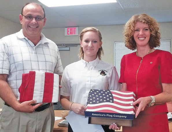 Mariposa County High School Grizzly Band senior drum major Sierra Dearing, center, presents the flag that was flown over the U.S. Capitol building to former Mariposa County Unified School District board president Joe Cardoso, left, and superintendent Robin Hopper.