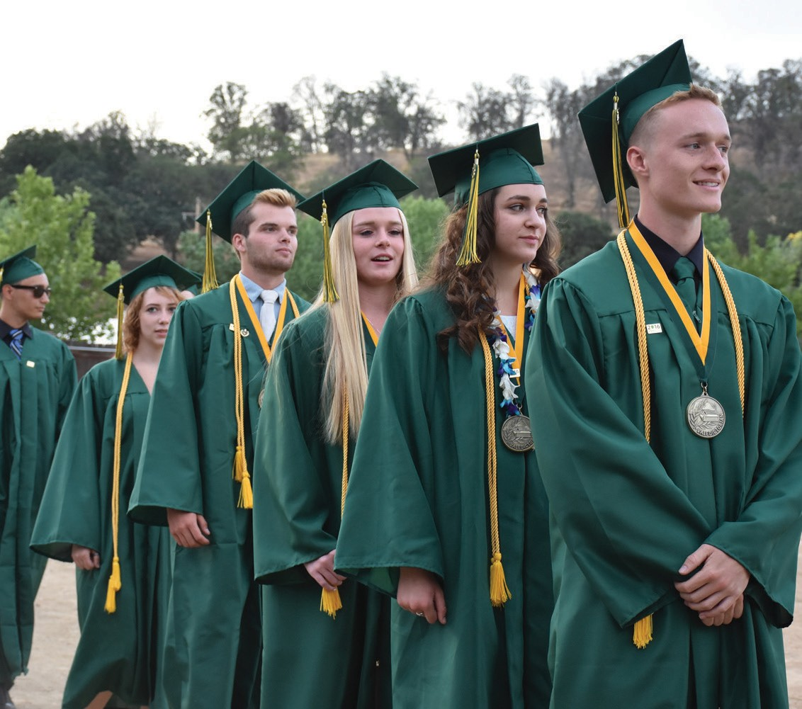 Lukas Hart, far right, leads one side of students into the Gold Bowl at the start of the ceremony. Hart was one of six valedictorians. He addressed the crowd later on, alongside fellow valedictorian Noah Rockwood (third from left).